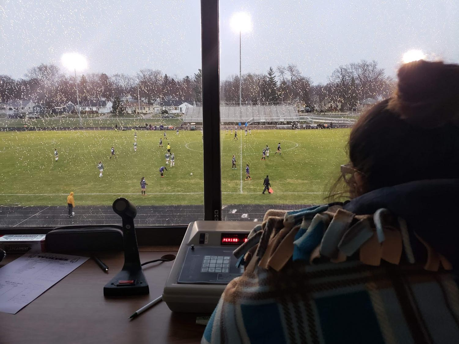 An overall picture with a close up of the scorekeeper and in the background the varsity game taking place.