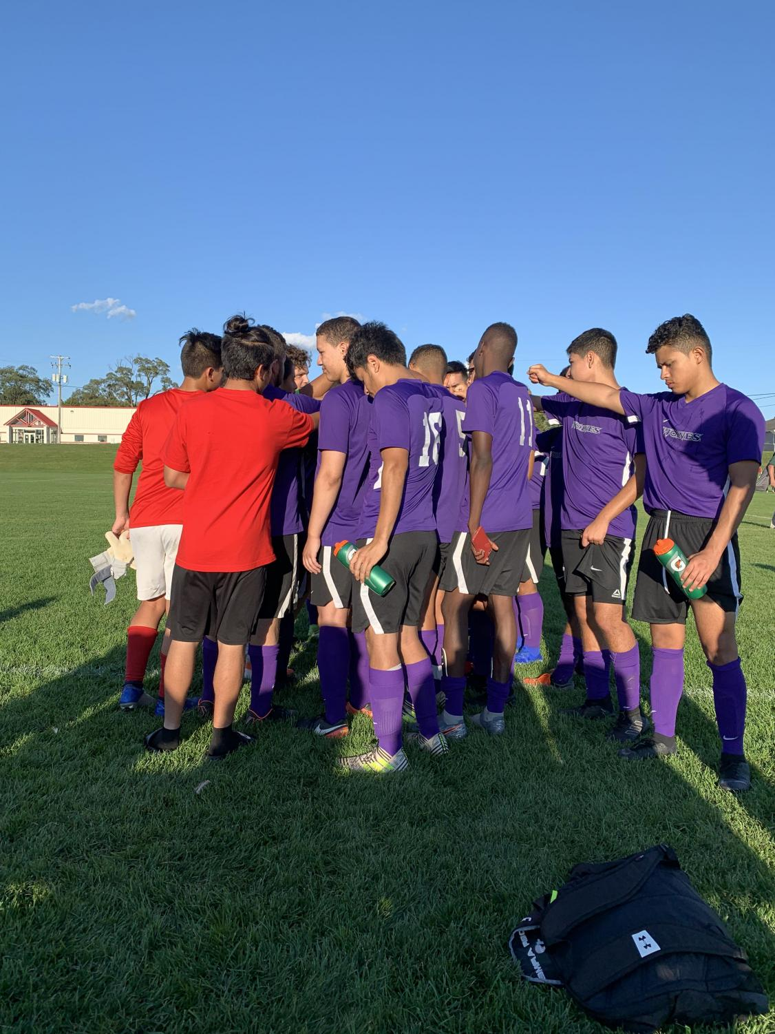 The soccer team huddles up before a game this season.